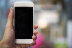 Χέρι Smartphone - χέρι ατόμων που κρατά το άσπρο smartphone με τη μαύρη οθόνη - που χρησιμοποιεί το κινητό τηλεφωνικό κενό στοκ φωτογραφία με δικαίωμα ελεύθερης χρήσης