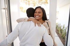 Χαιρετισμός ατόμων και αγκάλιασμα της συζύγου επιχειρηματιών δεδομένου ότι επιστρέφει το σπίτι από την εργασία στοκ φωτογραφίες