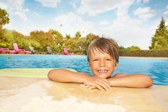 Χαλάρωση αγοριών χαμόγελου κοντά στην άκρη της πισίνας Στοκ Φωτογραφία