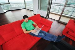 Χαλάρωση ατόμων στον καναπέ και εργασία για το φορητό προσωπικό υπολογιστή Στοκ Εικόνες