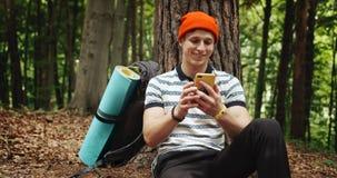 Χαλάρωση ατόμων στο δάσος κοντά στο δέντρο με το τηλέφωνο φιλμ μικρού μήκους