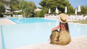 Χαλάρωση γυναικών από τη λίμνη σε ένα θέρετρο ξενοδοχείων πολυτελείας που απολαμβάνει τις τέλειες διακοπές παραθαλάσσιων διακοπών απόθεμα βίντεο
