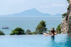 Χαλάρωση γυναικών στην πισίνα απείρου που εξετάζει την άποψη στοκ εικόνα με δικαίωμα ελεύθερης χρήσης