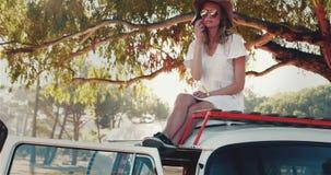 Χαλάρωση γυναικών στη στέγη αυτοκινήτων μια ηλιόλουστη ημέρα 4k φιλμ μικρού μήκους