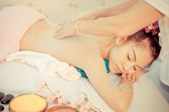 Χαλάρωση γυναικών στο κρεβάτι SPA ενώ ο θεράπων την τρίβει πίσω στοκ εικόνα
