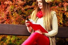 Χαλάρωση γυναικών στο φθινοπωρινό βιβλίο ανάγνωσης πάρκων Στοκ εικόνα με δικαίωμα ελεύθερης χρήσης