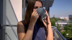 Χαλάρωση γυναικών στο φλυτζάνι εκμετάλλευσης μπαλκονιών, καφές κατανάλωσης φιλμ μικρού μήκους
