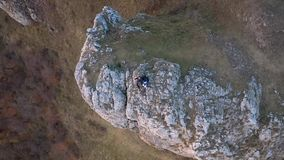 Χαλάρωση ζεύγους σε έναν απότομο βράχο βουνών Εναέριος κινηματογράφος κηφήνων 4k απόθεμα βίντεο