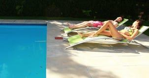 Χαλάρωση ζεύγους στην καρέκλα σαλονιών στο poolside απόθεμα βίντεο