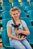 Χαλάρωση κοριτσιών χαμόγελου με το σκυλί το παιδί κοριτσιών στα καθίσματα του σταδίου Στοκ Φωτογραφία