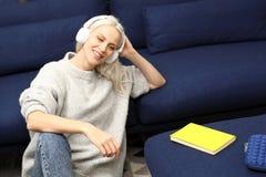 χαλάρωση Μια γυναίκα που χαλαρώνει ακούοντας τη μουσική στα ακουστικά στοκ εικόνες