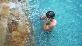 Χαλάρωση νεαρών άνδρων στην πισίνα κάτω από τον καταρράκτη λιμνών, σε αργή κίνηση 1920x1080 απόθεμα βίντεο