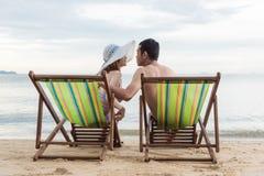 Χαλάρωση οικογενειακού ταξιδιού πολυτέλειας ζεύγους στην τροπική παραλία καρεκλών στοκ εικόνα με δικαίωμα ελεύθερης χρήσης
