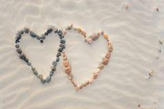 Χαλίκια που τακτοποιούνται στη μορφή δύο καρδιών στους κυματισμούς παραλιών άμμου Στοκ Φωτογραφίες