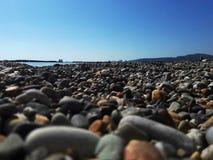 Χαλίκια στην κινηματογράφηση σε πρώτο πλάνο παραλιών θάλασσας με το θολωμένο υπόβαθρο της θάλασσας Παραλία χαλικιών στοκ εικόνες με δικαίωμα ελεύθερης χρήσης