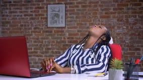 Χαλαρωμένη αφρικανική επιχειρηματίας που εργάζεται στο lap-top της καθμένος την ψύχρα με τον κόκκινο τοίχο πίσω απόθεμα βίντεο