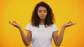Χαλαρωμένη γυναίκα αναμιγνύω-φυλών που αναπνέει βαθειά και που κάνει την άσκηση γιόγκας, αρμονία απόθεμα βίντεο