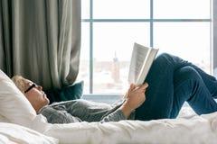 Χαλαρωμένη γυναίκα με τα γυαλιά που βρίσκονται σε ένα κρεβάτι που διαβάζει ένα βιβλίο εκτός από ένα μεγάλο παράθυρο Στοκ Εικόνες