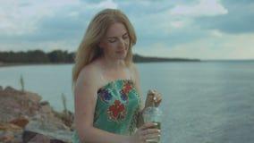Χαλαρωμένη γυναίκα που απολαμβάνει το κοκτέιλ mojito στην παραλία απόθεμα βίντεο