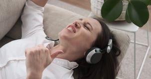 Χαλαρωμένη γυναίκα που τραγουδά και που ακούει τη μουσική στα ακουστικά στον καναπέ απόθεμα βίντεο