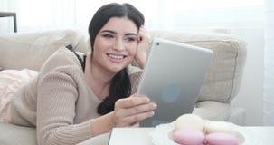 Χαλαρωμένη γυναίκα που χρησιμοποιεί την ψηφιακή ταμπλέτα στον καναπέ απόθεμα βίντεο
