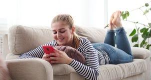 Χαλαρωμένη γυναίκα που χρησιμοποιεί το κινητό τηλέφωνο στο σπίτι απόθεμα βίντεο