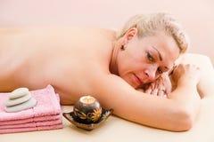 Χαλαρωμένη γυναίκα στον πίνακα μασάζ που λαμβάνει την επεξεργασία ομορφιάς day spa στοκ εικόνες
