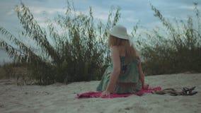 Χαλαρωμένη γυναίκα στο ψαθάκι που απολαμβάνει τον ελεύθερο χρόνο στην παραλία απόθεμα βίντεο