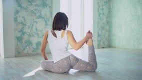 Χαλαρωμένη γυναίκα brunette που κάνει τη γιόγκα στο καθιστικό φιλμ μικρού μήκους