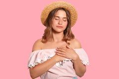 Χαλαρωμένη η ηρεμία γυναίκα κρατά τα χέρια στην καρδιά, εκφράζει την ευγνωμοσύνη, που αγγίζεται ή εντυπωσιασμένος από την καρδιά  στοκ εικόνα με δικαίωμα ελεύθερης χρήσης