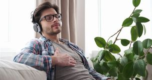 Χαλαρωμένη μουσική ακούσματος ατόμων στα ακουστικά στο σπίτι απόθεμα βίντεο