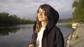 Χαλαρωμένη νέα γυναίκα που ακούει τη μουσική και που χορεύει κοντά σε έναν ποταμό φιλμ μικρού μήκους