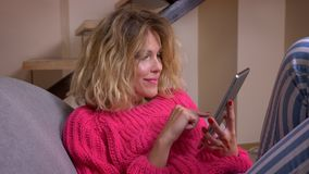 Χαλαρωμένη νοικοκυρά στη ρόδινη συνεδρίαση πουλόβερ στον καναπέ που κάνει σερφ στην ταμπλέτα και συναισθηματικά που αντιδρά στην  απόθεμα βίντεο