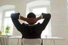 Χαλαρωμένη στήριξη αφροαμερικάνων που κλίνει πίσω στην καρέκλα στοκ φωτογραφία με δικαίωμα ελεύθερης χρήσης