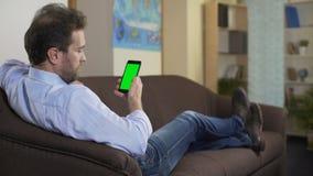 Χαλαρωμένη συνεδρίαση προσώπων στον καναπέ και έρευνα του ξενοδοχείου για τις διακοπές στο smartphone φιλμ μικρού μήκους