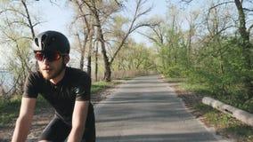 Χαλαρωμένος αθλητικός κατάλληλος ποδηλάτης που οδηγά ένα ποδήλατο στο πάρκο Το μέτωπο ακολουθεί τον πυροβολισμό Γενειοφόρος ποδηλ απόθεμα βίντεο