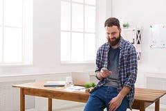 Χαλαρωμένος νέος επιχειρηματίας που χρησιμοποιεί κινητό στην αρχή Στοκ εικόνες με δικαίωμα ελεύθερης χρήσης