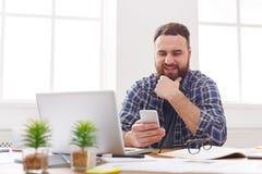 Χαλαρωμένος νέος επιχειρηματίας που χρησιμοποιεί κινητό στην αρχή Στοκ Εικόνες
