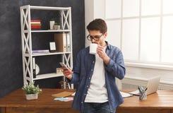 Χαλαρωμένος νέος επιχειρηματίας που χρησιμοποιεί κινητό στην αρχή Στοκ φωτογραφίες με δικαίωμα ελεύθερης χρήσης
