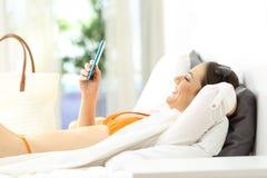 Χαλαρωμένος φιλοξενούμενος ξενοδοχείων που χρησιμοποιεί ένα τηλέφωνο στις διακοπές στοκ εικόνα