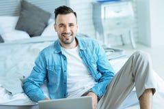 Χαλαρωμένος χιλιετής κύριος με το lap-top που χαμογελά για τη κάμερα Στοκ εικόνες με δικαίωμα ελεύθερης χρήσης