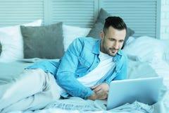 Χαλαρωμένος χιλιετής τύπος που βρίσκεται στο κρεβάτι με το lap-top Στοκ φωτογραφία με δικαίωμα ελεύθερης χρήσης