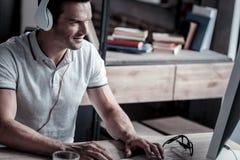Χαλαρωμένος χιλιετής τύπος που δακτυλογραφεί και που ακούει τη μουσική Στοκ φωτογραφία με δικαίωμα ελεύθερης χρήσης