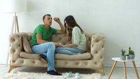 Χαλαρωμένο ζεύγος που μιλά μαζί να καθίσει στον καναπέ φιλμ μικρού μήκους