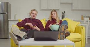 Χαλαρωμένο ζεύγος που προσέχει τη σε απευθείας σύνδεση TV στο lap-top φιλμ μικρού μήκους
