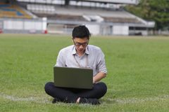 Χαλαρωμένο νέο ασιατικό επιχειρησιακό άτομο που εργάζεται με το lap-top στην πράσινη χλόη Στοκ Εικόνες