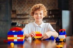 Χαλαρωμένο παιδί που απολαμβάνει το παιχνίδι με το σύνολο κατασκευής Στοκ Εικόνες