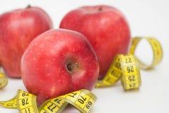 Χαλαρός ζυγίστε Τρεις κόκκινη Apple με την ταινία μέτρου για, στη μέση της εικόνας, τη διατροφή και την ικανότητα με το διάστημα  Στοκ Εικόνες