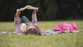 Χαλαρώνοντας ανάγνωση στη χλόη απόθεμα βίντεο