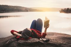 Χαλαρώνοντας ασιατικός τουρίστας στιγμής που διαβάζει ένα βιβλίο στο βράχο στοκ φωτογραφία με δικαίωμα ελεύθερης χρήσης